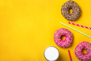 Wall Mural - Yellow dessert background with various donuts and milk