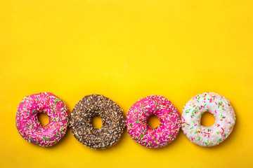 Wall Mural - Four donuts in line on yellow background
