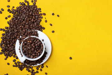 Coffee cup with beans on yellow background.