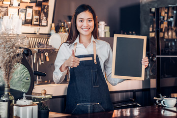 Asian female barista wear jean apron thumbs up at blank blackboard coffee menu at counter bar with smile face,cafe service concept,business owner start upLeave space for adding your text..