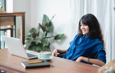 asia woman relax after working,female watching live streaming video on laptop drink coffee cup on wood table in cafe restaurant,working lifestyle outside office,chill out leisure.