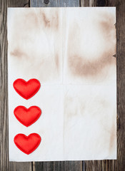 blank old paper with three red hearts