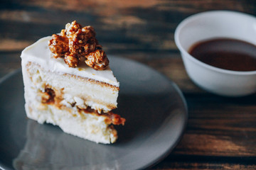 Slice of cheesecake topped with caramel popcorn on the wooden background. Artwork. Soft focus on caramel popcorn