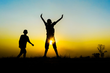Silhouette of children jumping on sunset.