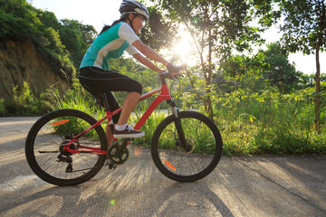 woman cyclist cycling on sunrise forest trail