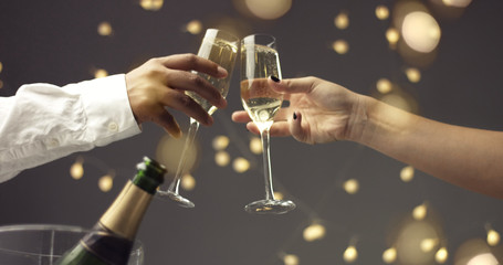 Close up of dark skinned man and caucasian woman toasting with glasses of sparkling wine on gray background with lights and lens flare