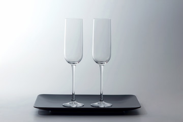 two empty wine glass on a brown plate on light background