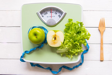 Green apple, fresh vegetable with weight scale and measuring tape for the healthy diet slimming . Diet and Healthy Concept