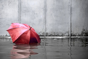 Red umbrella floating concept. Flooded on street. .Waiting for help me after the rain. Black and white colors. Close up.