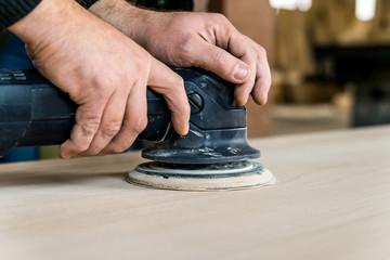 Close up man sanding wood in workshop