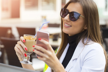 Fashion happy woman with sunglasses using a smartphone
