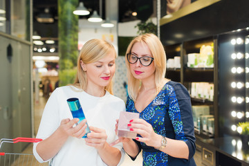 two blonde women choose products in the store