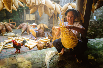 Vietnamese fishermen are doing basketry for fishing equipment at morning in Thu Sy Village, Vietnam. Wall mural