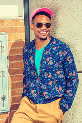 African American Man Street Fashion in New York, wearing blue patterned, collarless jacket, green V neck shirt, yellow brown pants, pink cap, sunglasses, standing against wall under sun, smiling..
