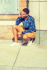 African American Man traveling in New York, wearing blue patterned jacket, yellow brown shorts, white sneakers, squatting in corner of street, smiling, talking on cell phone. Modern Daily Life..