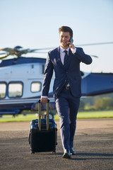 Businessman Walking Away From Helicopter Whilst Talking On Mobile Phone