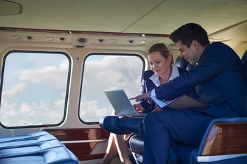 Businessman And Businesswoman Working On Laptop In Helicopter Cabin