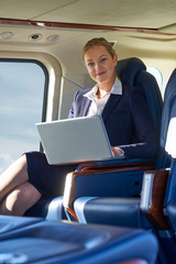 Portrait Of Businesswoman Working On Laptop In Helicopter Cabin During Flight