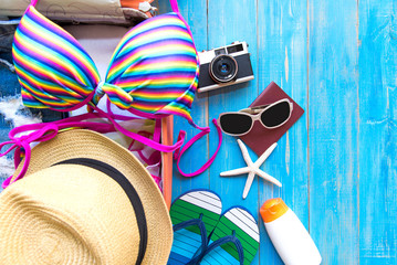 Summer traveling with old suitcase and Fashion woman swimsuit Bikini, fish star, sun glasses, hat. Travel in the holiday, sunset beach background.  Summer and Travel Concept.
