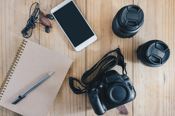 Top view of travel object : gray pencil on brown notebook. and white mobilephone, earphone, black camera and two lens on wooden table