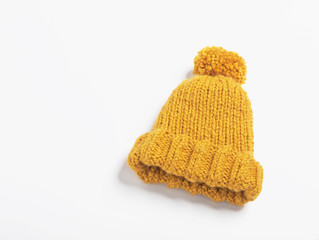 Mustard knit beanie hat with big pom pom isolated on white background. Copy space.