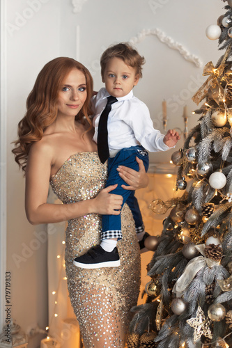 happy mother and baby sitting near the luxury decorated christmas