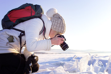 Portrait of female photographer shooting winter landscape next to the frozen lake Baikal. Winter tourism in Russia