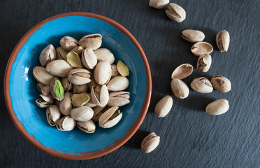 roasted pistachios in a bowl on slate surface