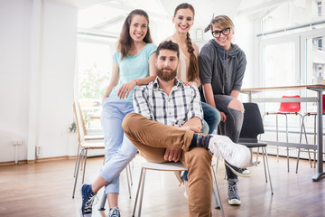 four co-workers wearing casual clothes during work in a modern hub for freelancers