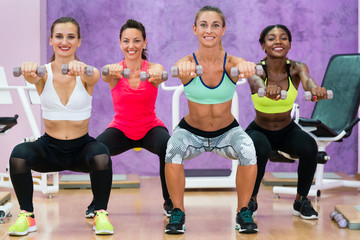 women doing squats holding dumbbells at functional training group class for ladies