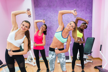 Four cheerful women holding dumbbells while doing exercises during group fitness class