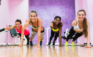 Happy women showing thumbs up from plank position as a like sign for a trendy fitness club