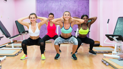 women doing squats during workout group class in modern health club for ladies only