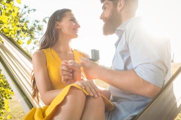 Young man making marriage proposal to beautiful girlfriend while swinging in hammock