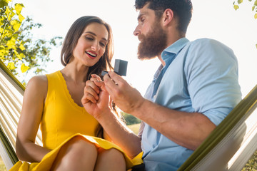 Happy man putting engagement ring on the finger of girlfriend on summer day