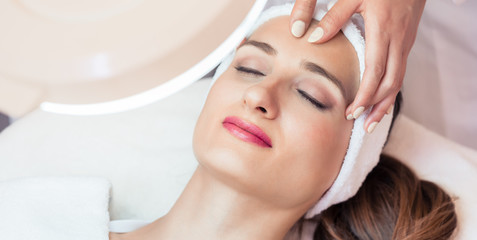 Relaxed woman smiling under the benefits of anti-aging facial massage