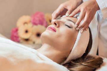 Beautiful woman relaxing during rejuvenating facial massage in a modern beauty center