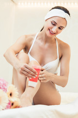 Fit woman waxing her legs with a portable roll-on depilatory wax heater