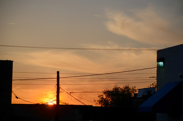 The silhouettes of the tops of buildings and utility wires are visible as the sun sets in downtown Anniston, Alabama, USA