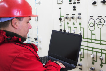 Technician in red with laptop reading instruments in power plant control center