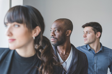 portrait of three young multiethnic man and woman looking over - creative people, pensive, inspiration concept