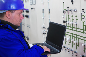Technician in blue with laptop reading instruments in power plant control center