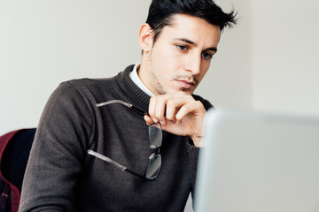 Young handsome contemporary businessman holding glasses while using computer - technology, business concept