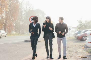 Three multiethnic woman and men friends walking outdoor in city back light, chatting and holding smart phone - friendship, social network, conversation concept