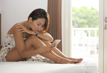 attractive Asian woman sitting on bed at home bedroom in front of the window texting with mobile phone relaxed