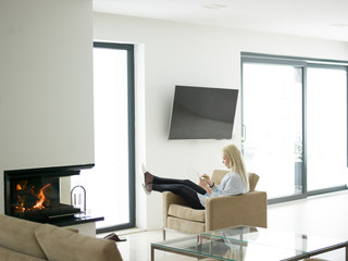 young woman using tablet computer in front of fireplace