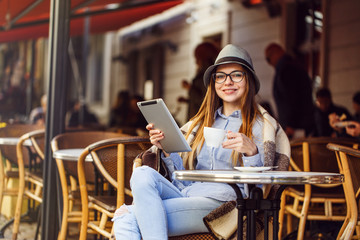 Stylish cheerful girl wears blue shirt, hat and eyeglasses, plaid, having cup of coffee using tablet pc in street cafe, outdoors sunny autumn time