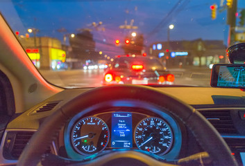 Car dashboard and city traffic at night