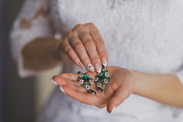 Earrings with green stones in the womens hands 8828.