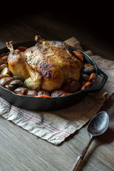 whole baked chicken with potatoes and carrots in cast iron with spoon